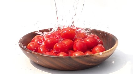 Fototapete - Pouring fresh water to the pile of Cherry Tomatoes on white background in Slow Motion