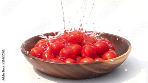 Fototapete Pouring fresh water to the pile of Cherry Tomatoes on white background in Slow Motion