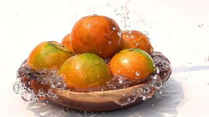 Fototapete - Pouring fresh water on a pile of oranges in wooden bowl on white background in Slow Motion