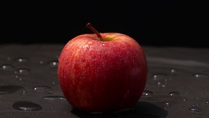 Fototapete - Drop fresh water on a red apple on black background in Slow Motion