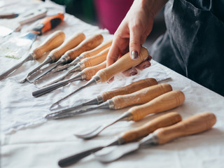 Art craft tools set arranged on table. Carving and modeling equipment. Woman hand choosing chisel.