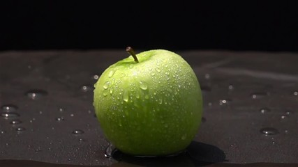 Fototapete - Water drop on a green apple on black background in Slow Motion