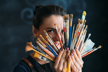 Artist and art supplies. Tools for talent. Smiling woman painter in apron posing with paintbrushes bunch. Wall mural