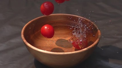 Fototapete - Hygenic Cherry Tomatoes falling to the water in wooden bowl in Slow Motion