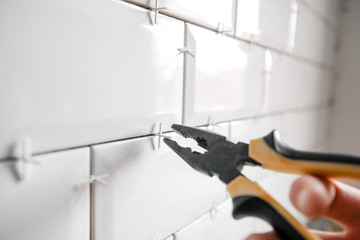 Ceramic tile lying. Installing new subway or metro tiles in bathroom, shower or kitchen back splash during home renovation. Placing or taking out tile spacers with hands and pliers.