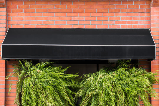 Black awning on brick wall with ferns hanging on window