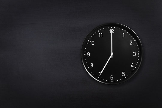 Black wall clock showing seven o'clock on black chalkboard background. Office clock showing 7am or 7pm on black texture