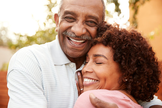 Senior black man and his middle aged daughter embracing, close up