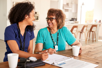 Female healthcare worker sitting at table smiling with a senior woman during a home health visit