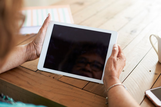 Over shoulder view of a senior woman's hands  holding a tablet computer, selective focus