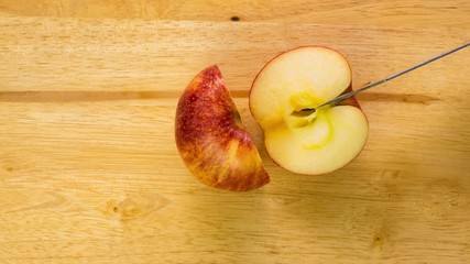 Fototapete - Cutting red apple on a wooden board, Stop Motion