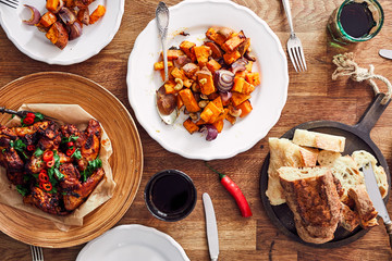 Overhead view of table served with traditional British Sunday roast dinner, featuring roasted chicken, squash and sweet potatoes