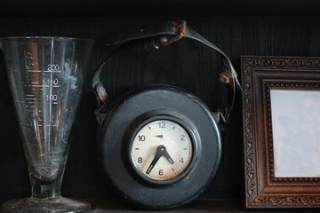 Old hang clock in black leather skin on shelf with other vintage decorations, old picture frame and measure science glass