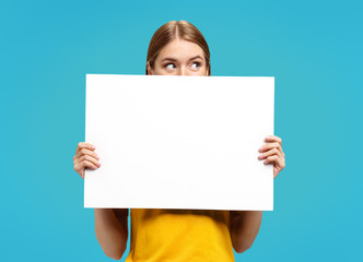 Funny girl with white empty poster, looking away, on blue background. Copy space for your text.
