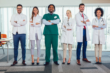 Multiethnic team of doctors in hospital looking at camera.