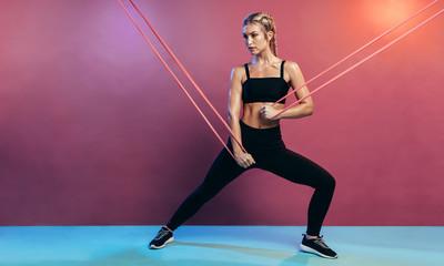 Fototapeta Strong athlete exercising with resistance band obraz