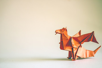 Origami dragon in red on a plain background. Paper Origami. Сopy space
