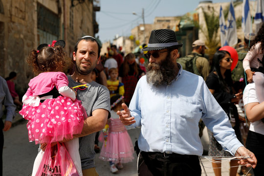 Baruch Marzel from the Jewish Power party walks with an Israeli settler as he carries a girl dressed-up in a costume during celebrations marking the Jewish holiday of Purim, in the Israeli-occupied West Bank city of Hebron