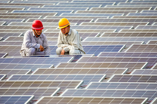Two Asian engineers carefully inspected solar photovoltaic panels floating on the water