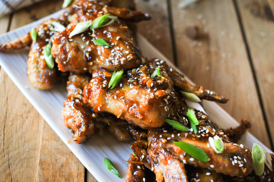 Close-up of crispy baked chicken wings, glazed with honey sauce with fresh scallions on wooden background