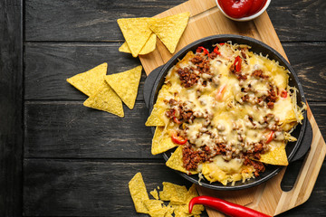 Tasty Mexican dish with nachos on table