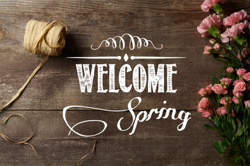 top view of ribbon, eustoma and carnation flowers on wooden surface with welcome spring illustration