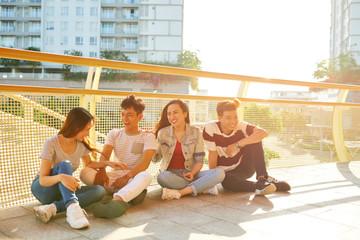 Cheerful friends sitting on bridge