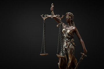 bronze statuette with scales of justice isolated on black