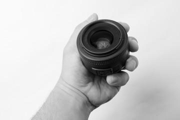 Mano sosteniendo un lente de cámara de fotos