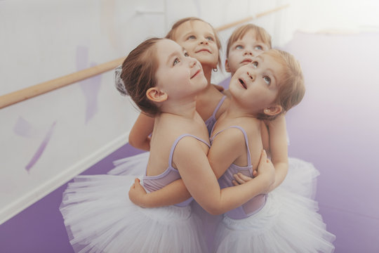 Adorable little girls in leotards and tutu skirts embracing, looking away joyfully. Group of cute young ballerinas having fun after ballet class, copy space. Friendship, childhood, sisterhood concept