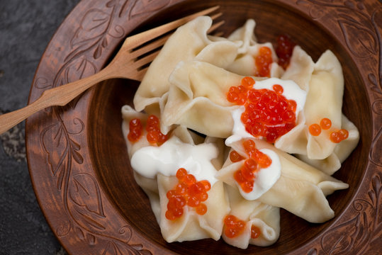Close-up of vareniki dumplings topped with sour cream and red caviar, view from above