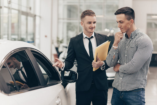 Professional car dealer showing cars on sale to his male customer, working at the auto dealership salon. Man looking thoughtfully at the car he is examining. Handsome man buying new automobile