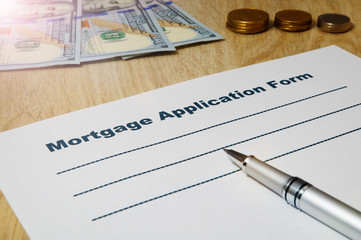 Mortgage application form with a pen and money.