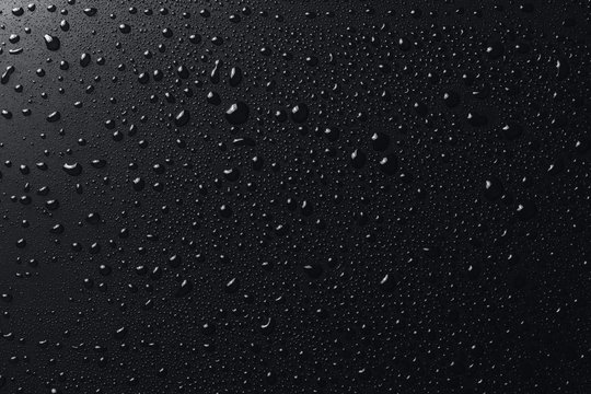 Shiny water drops on black surface, background