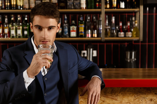 His look leaves you motionless. Handsome young man having a drink at the bar looking at the camera confidently copyspace on the side
