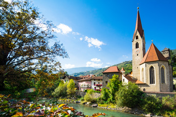 church and colorful houses along river Isarco, Chiusa, Italy