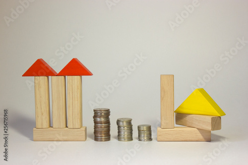 Toy house made of wooden blocks with coins  Property business