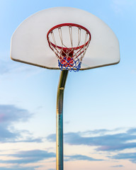 Basketball goal in a playground at twilight
