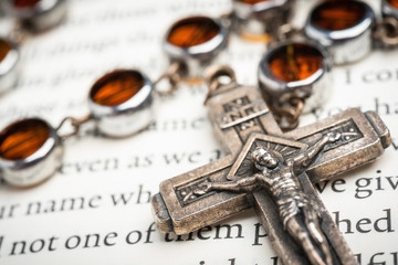 An extreme close up or macro shot with selective focus of a rosary with crucifix and glass beads in metal enclosures and chain set on a page of holy biblical text.