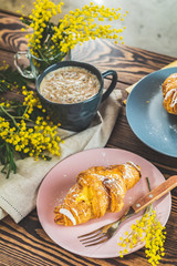 Breakfast with croissants, coffee and silver wattle