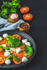 Italian caprese salad in black ceramic plate