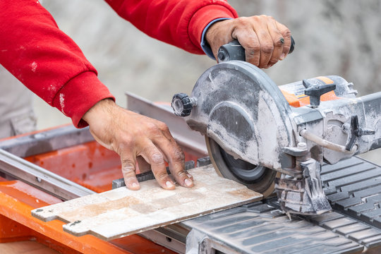 Worker Using Wet Tile Saw to Cut Wall Tile At Construction Site
