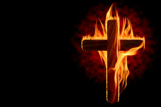 Cross burning or lighting concept theme with wooden crucifix engulfed in fiery flames isolated on black background with copy space. It was used as a declaration of war, to protest, to intimidate, etc