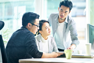 three young asian entrepreneurs discussing business in office