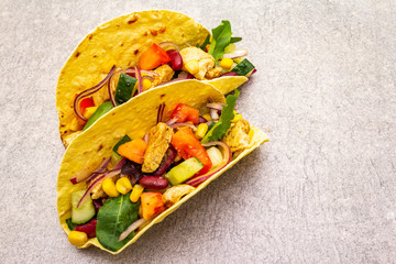 Mexican taco with chicken meat, red beans, fresh vegetables. Latin american food, stone background, close up.