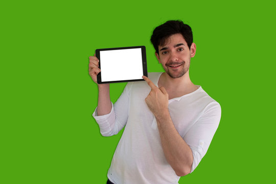 Picture of a Guy holding a tablet, pointing at it and showing it on a green screen background