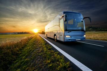 Fotobehang - Bus traveling on the asphalt road in rural landscape at sunset