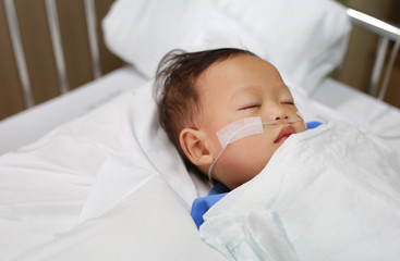 Close up Baby boy on patient bed with tube in nose to deliver oxygen. Respiratory support.