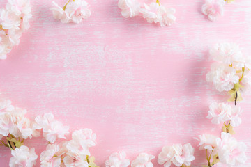 Spring background. Spring blooming branches on pink wooden background. Apple blossoms.