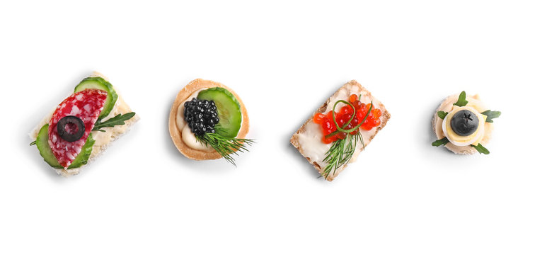 Assortment of tasty canapes on white background